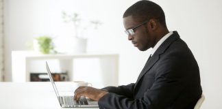 Man sitting at computer writing a rejection letter