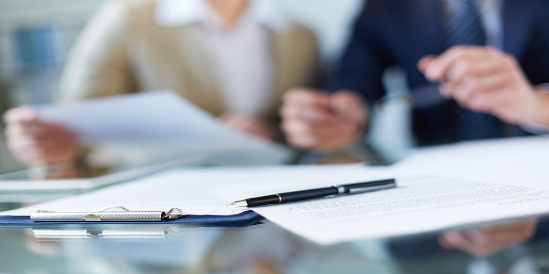 Business documents and pen at workplace detailing layoff severance package.