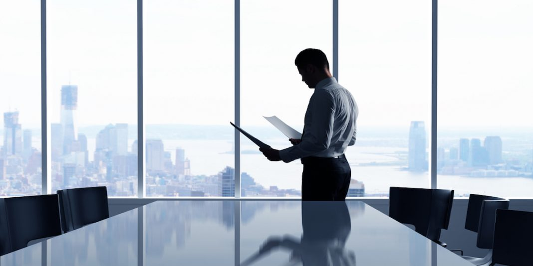 businessman in office overlooking the city thinking about major company layoffs.