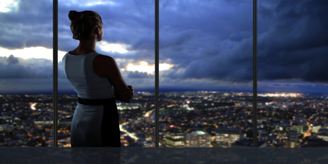 Woman employee overlooking city in office place thinking about severance package.