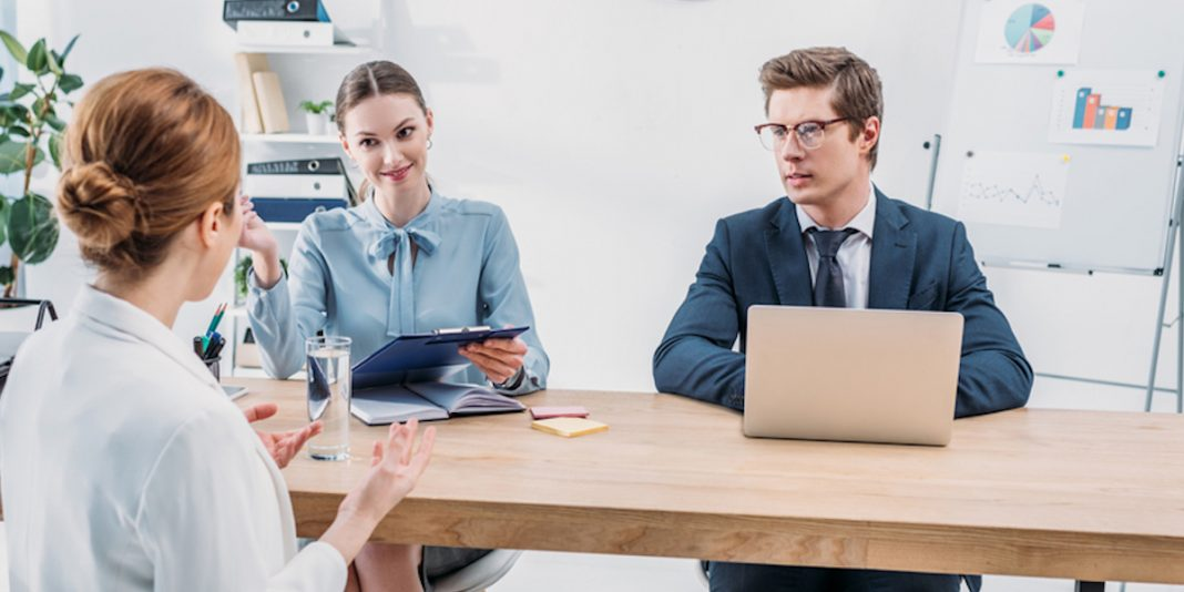 3 people in a job interview setting replicating the candidate experience.