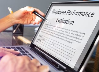 Close-up view of employee annual review form on laptop over office desk.