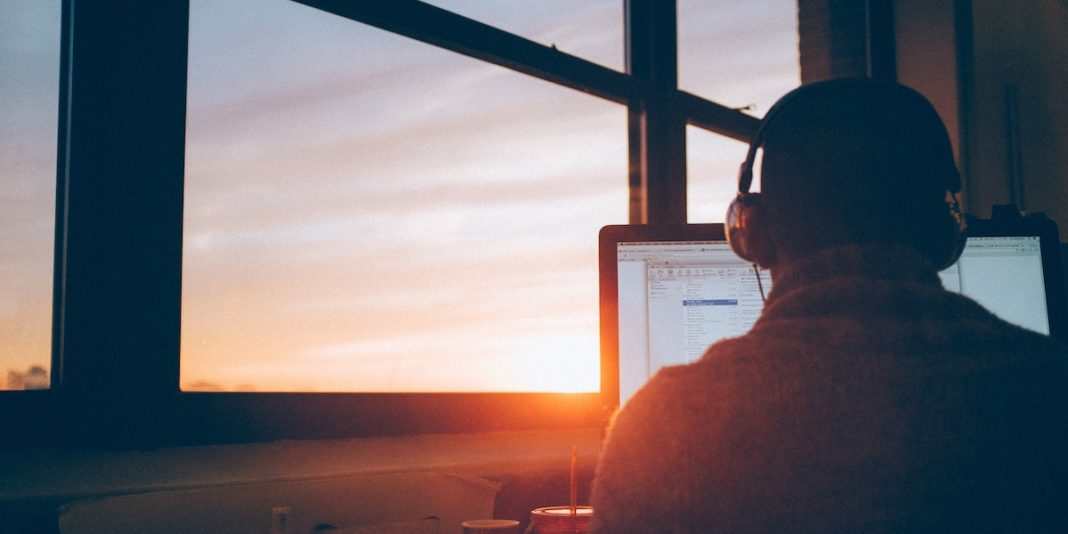 young man on laptop near a window, with a sunset, watching a human resources webinar on managing layoffs.