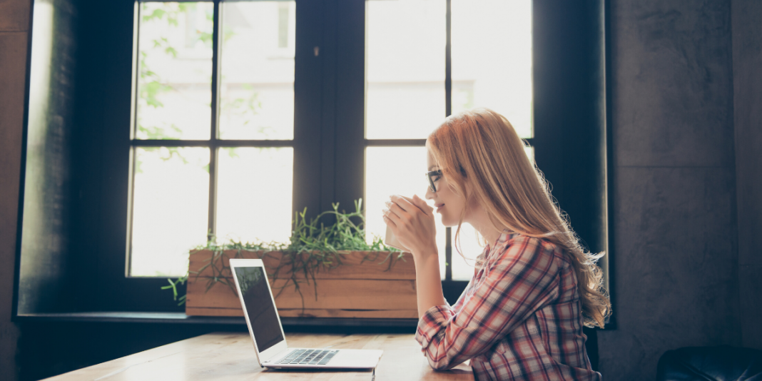 woman watching HR webinar on laptop at desk.