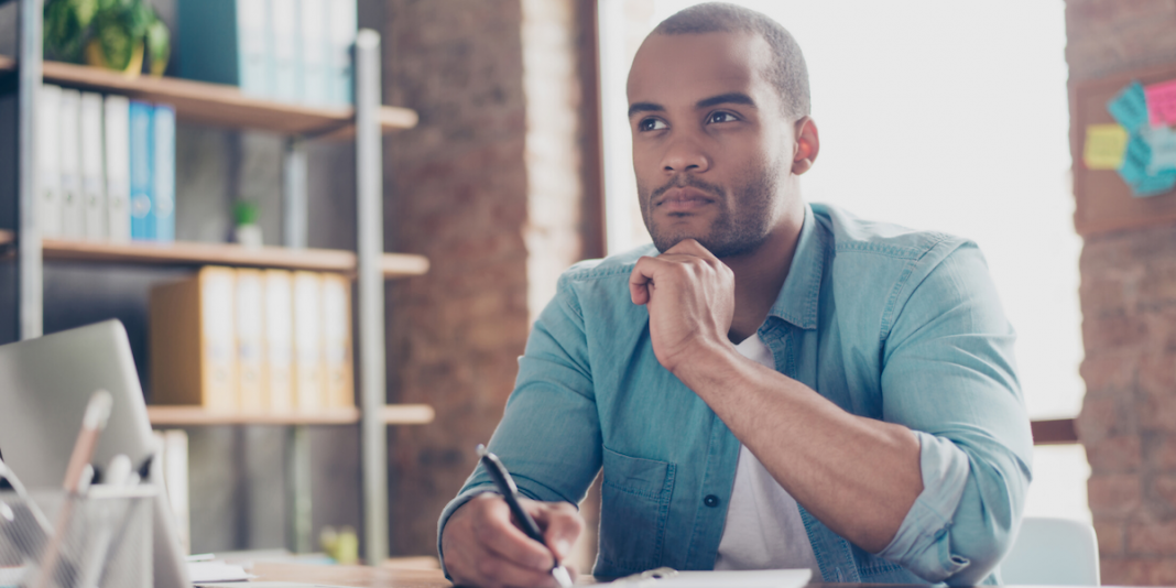 Man sitting at work desk at home, thinking about the list of decisions that will need to be made.